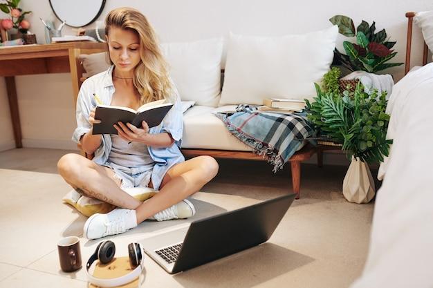 Ziemlich stilvolle junge frau, die mit geöffnetem laptop und tasse kaffee auf dem boden sitzt und im planer schreibt