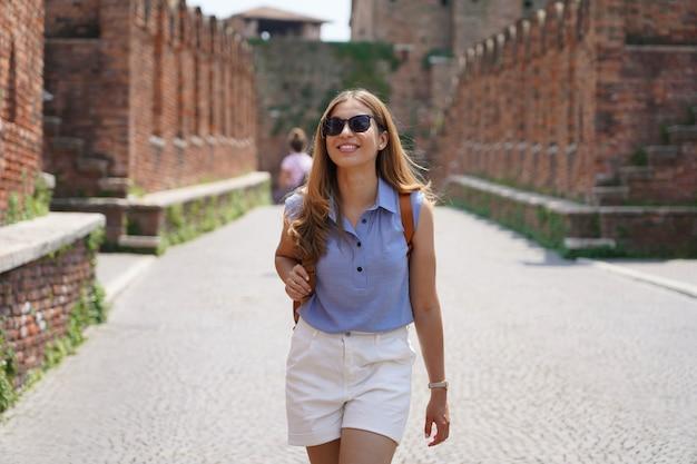 Ziemlich stilvolle touristenfrau, die in der mittelalterlichen stadt verona, italien, spaziert