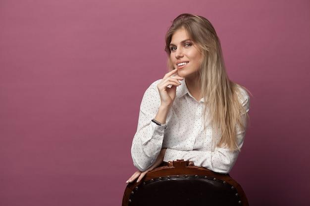 Ziemlich stilvolles mädchen mit den blonden haaren, die auf rosa aufwerfen. mode-mode-art-porträt der jungen glücklichen lächelnden frau