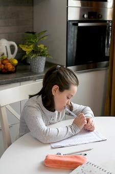 Ziemlich süßes schulmädchen 7-8 jahre alt, das zu hause studiert. heimschule, online-bildung, heimunterricht,