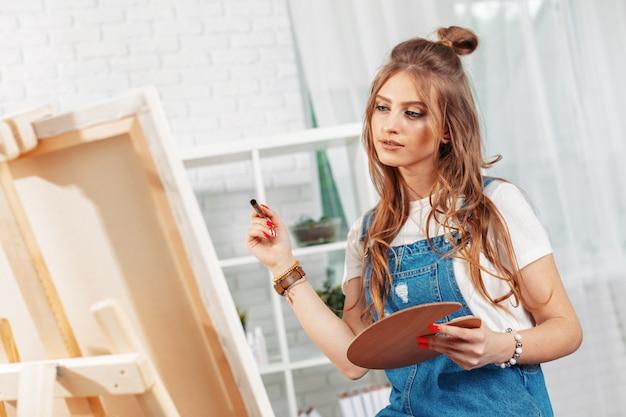 Ziemlich talentierte malerin malerei auf staffelei