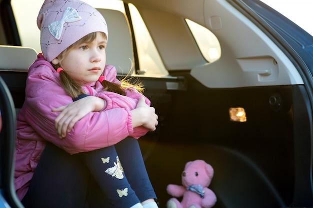 Ziemlich trauriges mädchen, das allein in einem autokofferraum mit einem rosa spielzeug-teddybär sitzt.