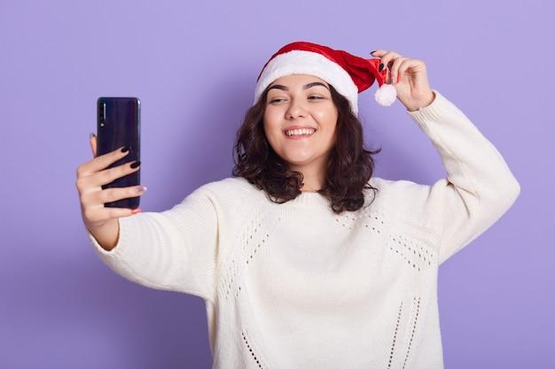 Ziemlich überglückliche dame, die selfie macht, strickpullover und weihnachtsmütze trägt, isoliert über lila wand posiert, frau, die smartphone hält und gerätebildschirm mit glücklichem lächeln betrachtet.