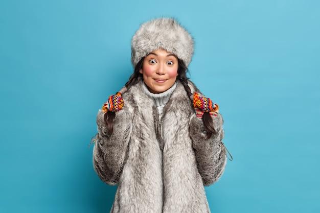 Ziemlich überraschte junge asiatische frau hält zöpfe in oberbekleidung über blaue wand isoliert. eskimofrau trägt hut und mantel lebt in der arktis