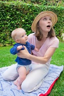 Ziemlich überraschte mutter, die mit offenem mund auf plaid im park sitzt und wegschaut. nettes baby im blauen hemd, das mit hilfe der mutter steht und beiseite schaut