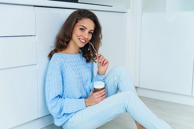 Ziemlich üppige junge frau in lässigen stilvollen kleidern, die leckere schokoladencreme genießen und kamera mit niedlichem lächeln im kücheninneren betrachten.