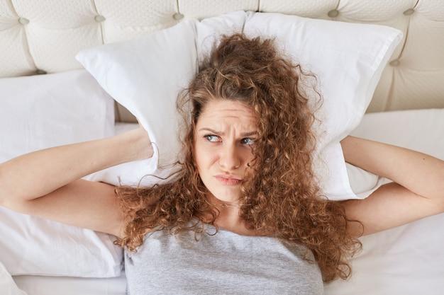 Ziemlich unzufriedene frau mit lockigen ohren bedeckt mit kissen, liegt im bett, hat schlaflosigkeit, kann wegen lärm nicht einschlafen, hat schlaflose nacht