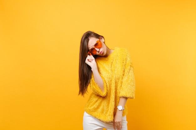 Ziemlich verärgerte junge frau in pelzpullover und weißer hose, die eine orangefarbene brille des herzens hält und die lippen einzeln auf hellgelbem hintergrund bläst. menschen aufrichtige emotionen, lifestyle-konzept. werbefläche.