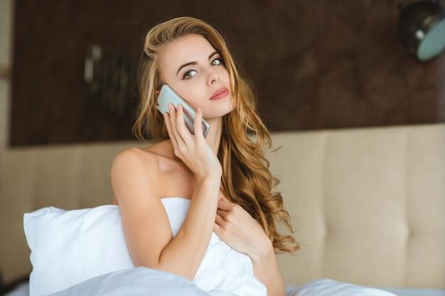 Ziemlich verführerische junge frau, die auf dem bett im schlafzimmer telefoniert