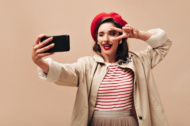 Ziemlich wunderbare frau mit braunem haar im roten hut, der zwinkert, friedenszeichen zeigt und selfie auf beige lokalisiertem hintergrund nimmt.