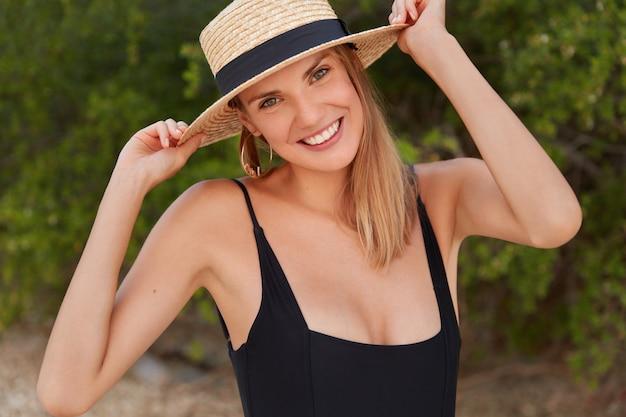 Ziemlich zufriedene frau mit strahlendem lächeln, trägt sommerstrohhut und schwarzen bikini, posiert im freien und freut sich über unvergessliche ferien im tropischen land. erfreute junge frau entspannt sich am strand