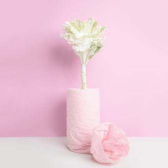Zierkohl in einer vase, eingewickelt mit rosa papier auf rosa wand