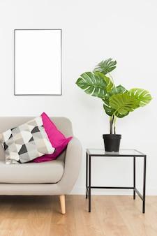 Zierpflanze mit leerem rahmen und sofa