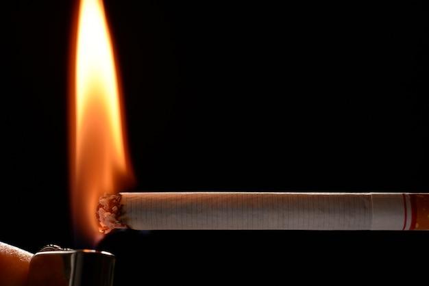 Zigarette, die durch kleine flamme auf schwarzem hintergrund angezündet wird