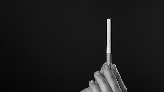 Zigarette in der hand in monochromem, rauchendem kopienraum.