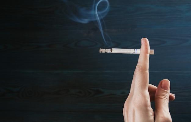 Zigarette in einer weiblichen hand auf einem hölzernen hintergrund in einem blauen dunstkopierraum. weibliches rauchen.