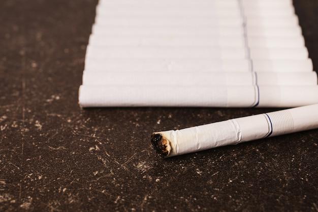 Zigaretten auf einem dunklen marmorhintergrund. schlechte angewohnheit. gesundheitsvorsorge