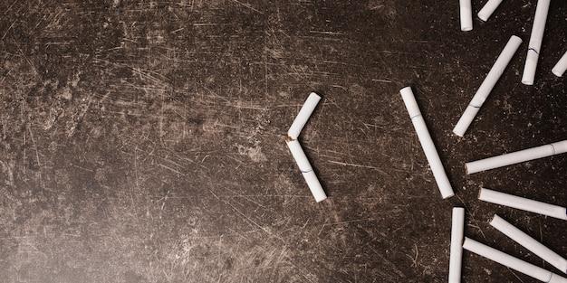 Zigaretten auf einem dunklen marmorhintergrund. schlechte angewohnheit. sorge für die gesundheit. hör auf zu rauchen