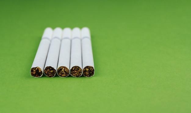 Zigaretten auf einem grünen hintergrund kopieren raum. ein paar zigaretten.