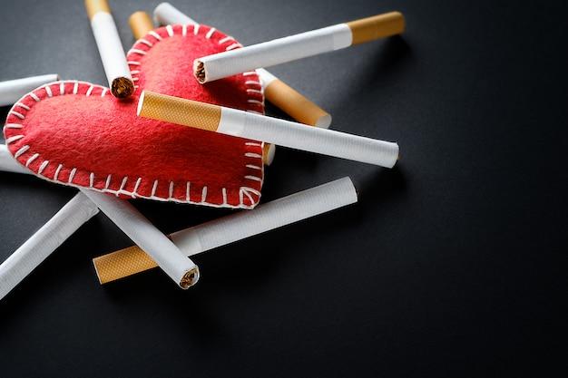 Zigaretten liegen auf einem roten dekorativen herzen, auf einem schwarzen hintergrund. rauchen zerstört die gesundheit. soziales problem.