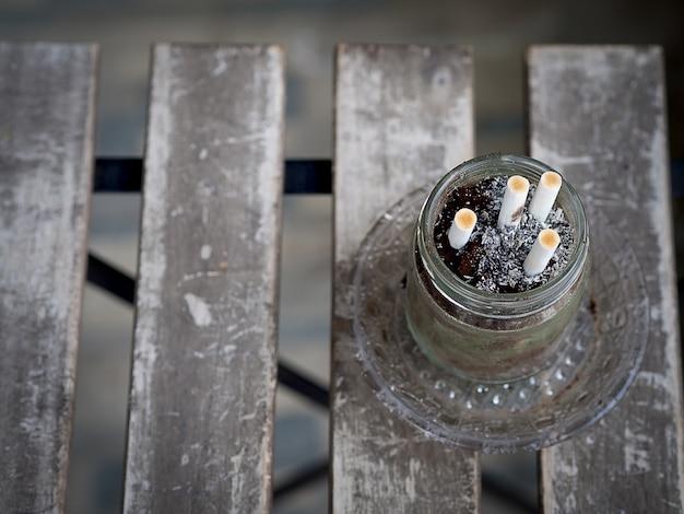 Zigaretten und schrotte im aschenbecher auf holztisch, schmutzig und rauchen, am raucherbereich