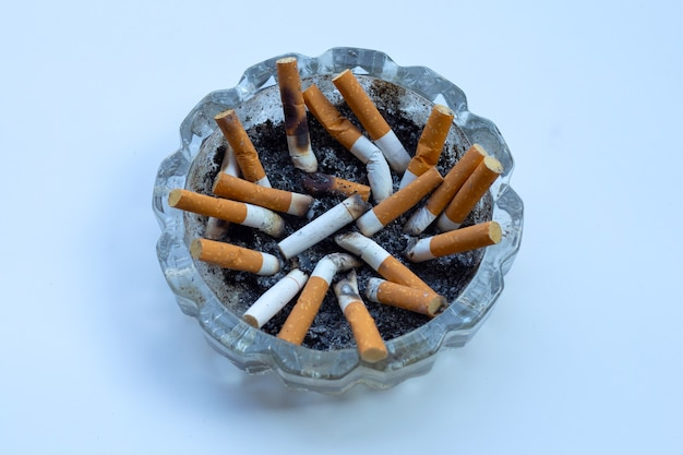 Zigarettenkippen im glasaschenbecher an der weißen wand.
