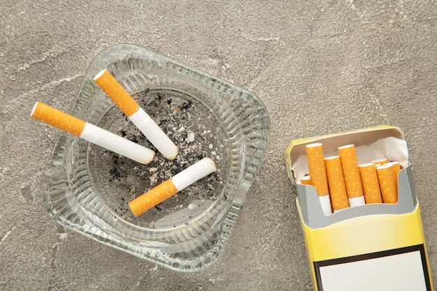 Zigarettenkippen mit asche im aschenbecher auf grauem betonhintergrund