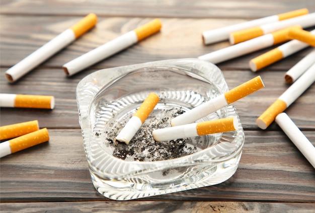 Zigarettenkippen mit asche im aschenbecher auf grauem holztisch