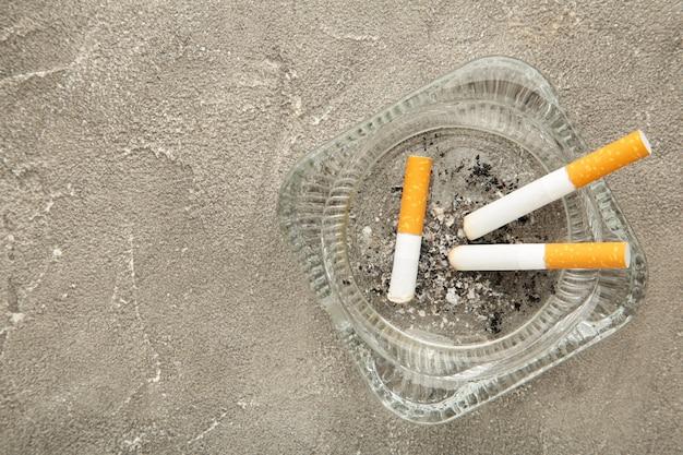 Zigarettenkippen mit asche im aschenbecher draufsicht