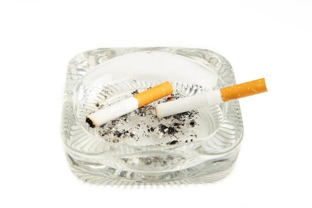 Zigarettenkippen mit asche im aschenbecher lokalisiert auf weißem hintergrund