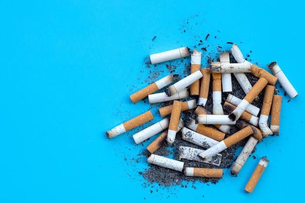 Zigarettenknospen mit aschenbecher auf blauer oberfläche