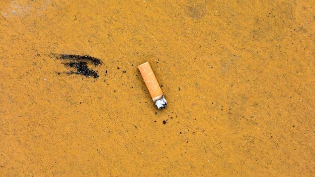 Zigarettenstummel auf schmutzigem gelbem boden