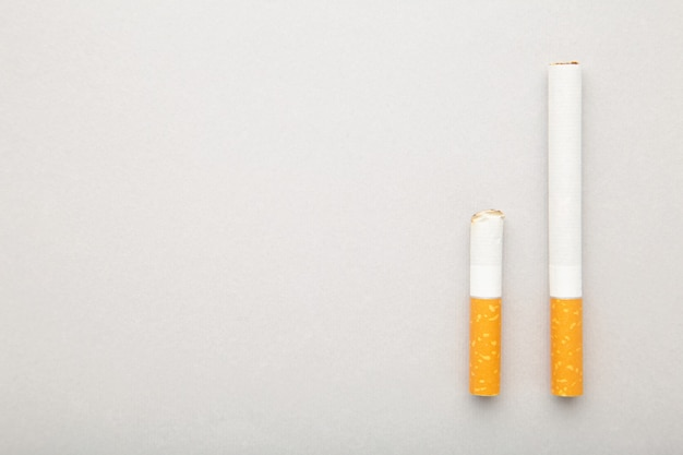 Zigarettenstummel mit zigarette auf grauem hintergrund