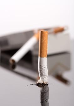 Zigarettenstummel und packung auf grau, studiobild