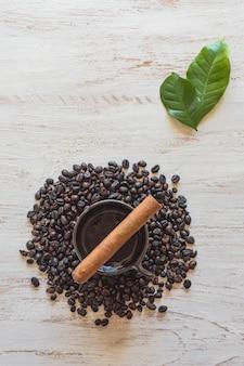Zigarre auf einer tasse schwarzen kaffees mit kaffeebohnen.