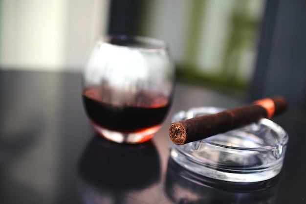 Zigarre mit einem glas alkohol auf einem schwarzen tisch