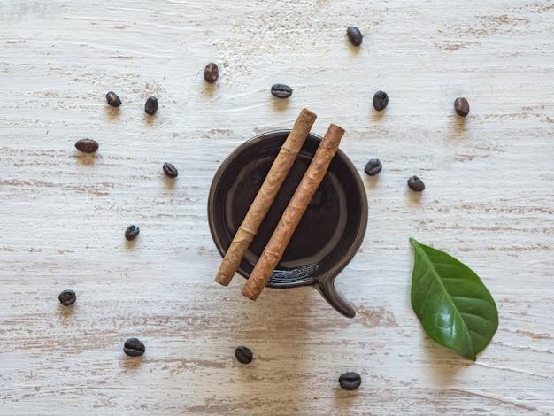 Zigarren auf einer tasse schwarzen kaffees mit kaffeebohnen.