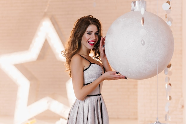 Zimmer dekoriert mit einem großen stern mit hintergrundbeleuchtung und einem riesigen weihnachtsball, junge frau in schönen stilvollen kleid
