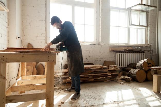 Zimmerei-werkstatt. mann mit elektrischen handsäge auf holzbohlen