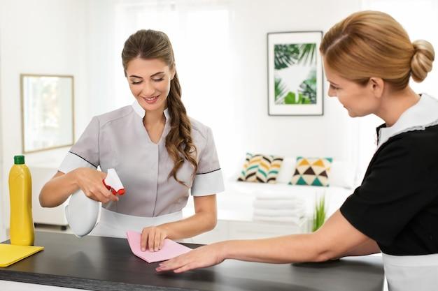 Zimmermädchen lehrt den auszubildenden, den tisch im zimmer von staub zu reinigen
