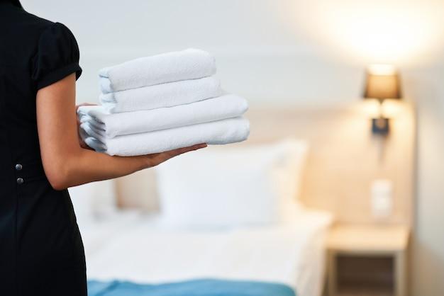 Zimmermädchen mit frischen handtüchern im hotelzimmer