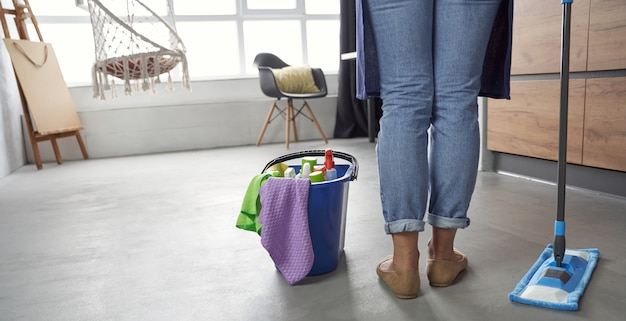 Zimmermädchen rückansicht der putzfrau mit mopp und plastikeimer mit lappen reinigungsmitteln und