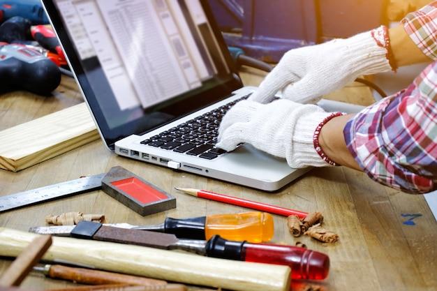 Zimmermann arbeitet mit laptop auf der werkbank in der tischlerei