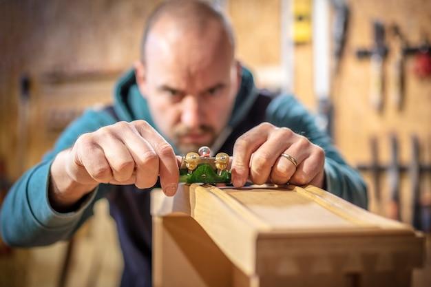 Zimmermann beabsichtigt, ein holzobjekt zu planen. selektiver fokus auf das werkzeug.