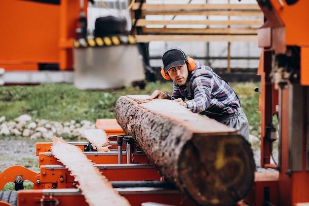 Zimmermann, der an einem sägewerk auf einer holzmanufaktur arbeitet