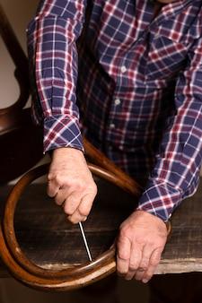 Zimmermann, der an einer hohen ansicht des stuhls arbeitet