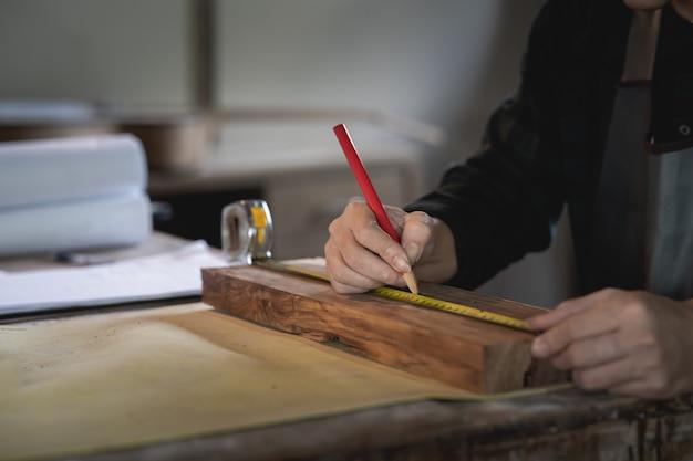 Zimmermann, der an holz in der tischlerei arbeitet. der mann arbeitet in einer tischlerei
