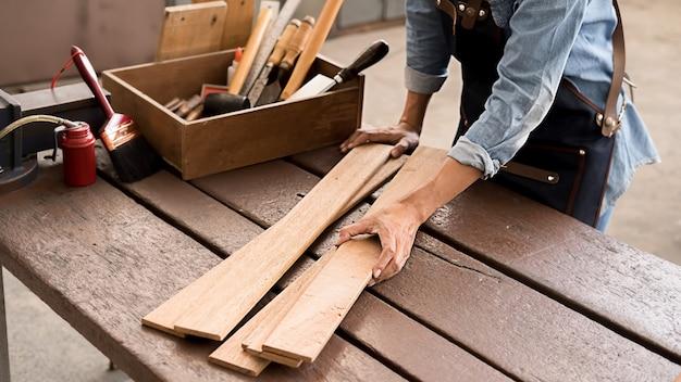 Zimmermann, der mit ausrüstung auf holztisch in der tischlerei arbeitet. frau arbeitet in einer tischlerei.