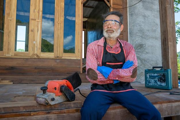 Zimmermann des älteren mannes, alter zimmermann, der in der tischlerwerkstatt arbeitet.