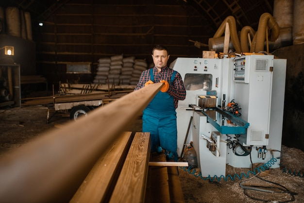 Zimmermann in uniform arbeitet an holzbearbeitungsmaschine, holzindustrie, zimmerei. holzfabrik